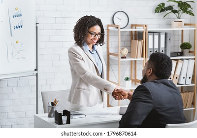 Black hiring manager shaking hands with successful vacancy candidate after work interview at modern office, copy space