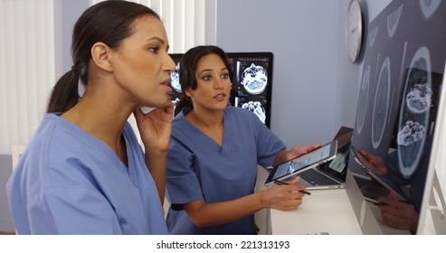 Black and hispanic female doctors working together with cell phone