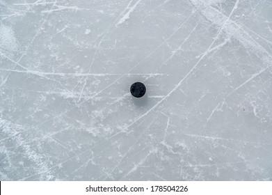 black hockey puck on ice rink.