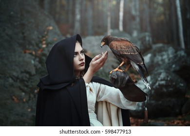 Black hooded huntress with hawk. Fantasy and falconry
