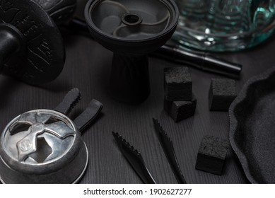 Black hookah on the table on a dark wooden background. Stylish oriental shisha. Shisha Concept. Egyptian hooka (calabash) details: water pipe, glass flask, silicone tobacco bowl, charcoals.