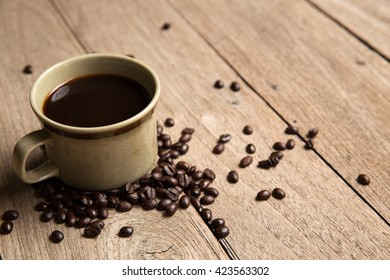 black hot coffee with coffee beans on wood background in the morning, start your day!