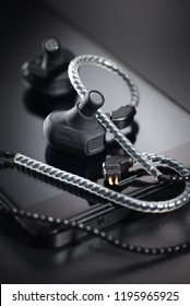 Black hybrid audiophile earbuds with balanced armature driver on smartphone