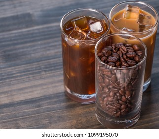 Black iced coffee, cold latte, and beans over wooden background