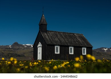 Black icelandic christian Budir church with blossoming flowers and deep blue sky