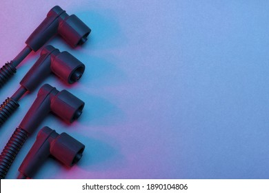 Black ignition wires of a high voltage for spark plug on blue and red background. Car parts. Top view.