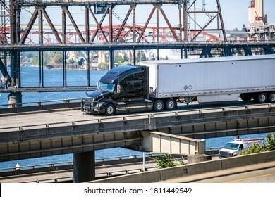 Black industrial grade diesel big rig semi truck transporting commercial cargo in dry van semi trailer running along the Willamette River in Portland on overpass highway road intersection