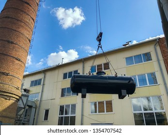 Black Industrial heat exchanger, tube shell and tube high efficiency. Transportation by the crane. Orange building. Red brick chimney. For any purpose use.