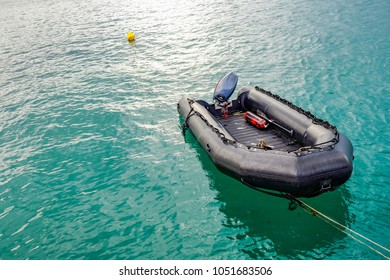 A black Inflatable Boat in the sea with a rope tied to the coast. on Boat there is an oxygen tank and a paddle