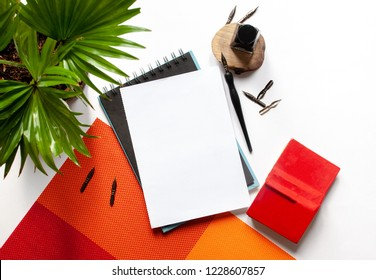 Black ink, ink bottle, green plant, red book and blank sketchbook page mockup and ink pen on a white background; top view, flat lay; overhead view