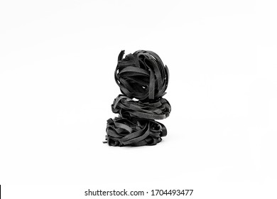 Black ink Italian pasta nests on white background