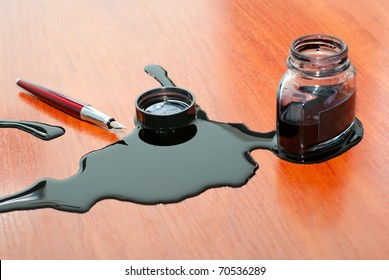 black ink spill near red pen on  table