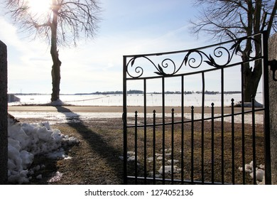 Black iron gate with ornament in front of snowy field in bright sunny light a winter day in Sweden.