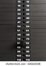 Black iron heavy plates stacked of weight machine with kilogram and pound number at fitness gym.