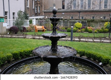 Black Iron Metal Fountain in Park with Water on Windy Overcast Day, Park in Background, Bright Vivid Green Grass, Focused, Movement of Water Droplets in Wind