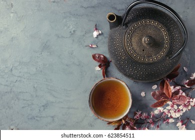 Black iron teapot and traditional ceramic cup of tea with blossom pink flowers cherry branch over gray blue metal texture background. Top view with space, Asian style.