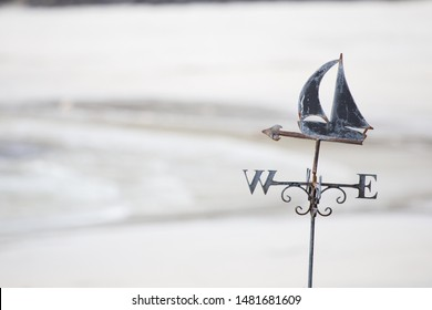 A black iron weathervane points due west.A metal arrow and sailing boat with sails decorates it. Deliberate blurred sand background.