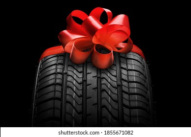 black isolation rubber tire, on the grey backgrounds in a bow for christmas - Shutterstock ID 1855671082