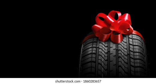black isolation rubber tire, on the grey backgrounds in a bow for christmas