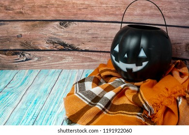 Black jack-o-lantern trick or treat candy bucket pail sitting on a cozy orange plaid blanket. Wood background. Concept for Halloween and fall