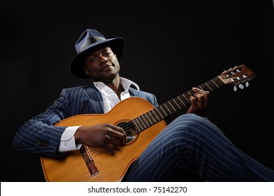 Black jazz musician wearing suit and blue hat playing guitar.