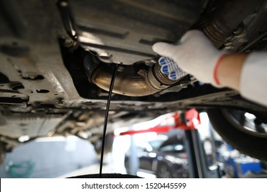 Black jet of used engine oil drains from the engine sump