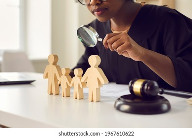 Black judge or lawyer looking in magnifying glass at little mom, dad children figures on desk. Family law court case investigation, divorce, joint custody of kid, parental rights deprivation concept - Shutterstock ID 1967610622