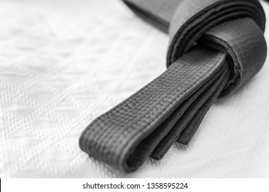 Black judo, aikido or karate belt on white kimono