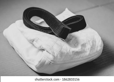 Black judo, aikido or karate belt on white judo gi