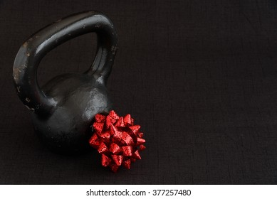 Black kettle bell with a red bow on a black background