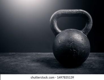 Black kettlebell on a black background