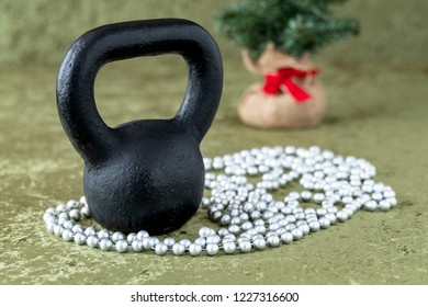 Black kettlebell on a green velvet background with silver bead garland, holiday fitness, Christmas tree in background