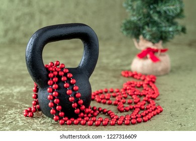 Black kettlebell on a green velvet background with red bead garland, holiday fitness, Christmas tree in background