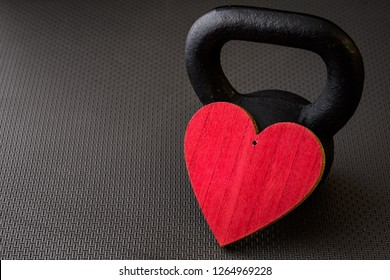 Black kettlebell on a black gym floor with large red heart to celebrate Valentine's Day fitness