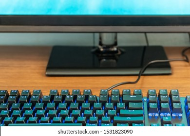 black keyboard with blue backlight next to the monitor on a wooden table