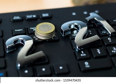 black keyboard. close-up. on it are laid out numbers of metal 2021 in the center of the coin 1 euro
