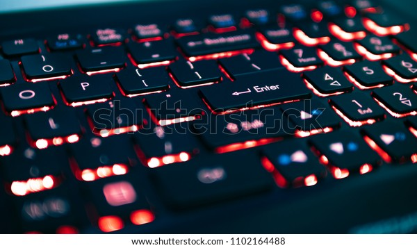 Black keyboard with red backlight, blurry close up, focus on enter key