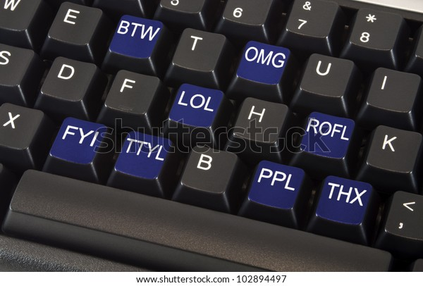 Black keyboard with text message slang words on keys including LOL, OMG, BTW, ROFL, FYI, TTYL, PPL and THX to illustrate fast paced social networking lifestyle concept.
