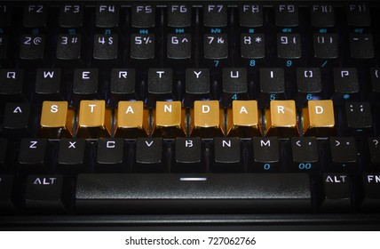 "Black keyboard with the word ""standard"" written in gold key caps."