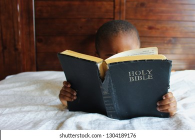 Black kid reading the Holy Bible.