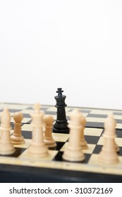Black king against white figures in the chess.