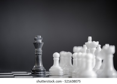 Black king on a chess board alone against all white pieces. Black king fights against white enemy team on board.