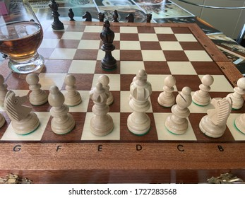 The black King on a chessboard before white pawns with a whisky glass