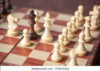 Black king surrounded by white chess pieces on a wooden chess board. Underdog concept.