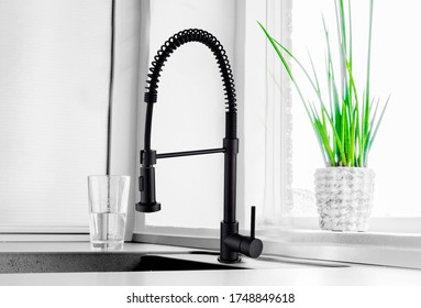 Black kitchen faucet on the silver sink near the glass of water