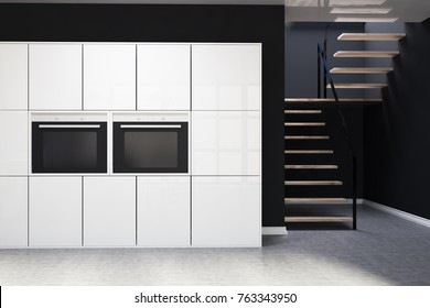 Black kitchen interior with a concrete floor, white cupboards with two built in ovens and a staircase. 3d rendering mock up