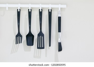 Black kitchen utensils hanging on white wall with copy space