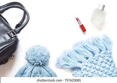 Black lady bag, blue knitted hat, woolen scarf, red lipstick and perfume bottle. Flat lay photo. Mockup for fashion blog, free space for text. Feminine style. Fall and winter season