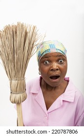 black lady with a broom looking surprised