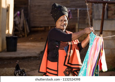 Black lady busy with the washing while wearing her traditional clothes